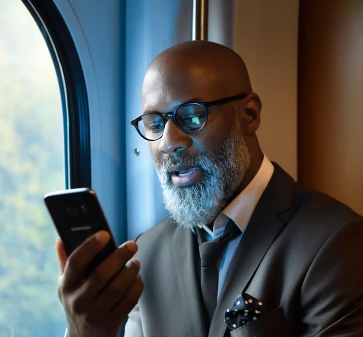 Geschäftsmann auf Bahnfahrt mit Smartphone