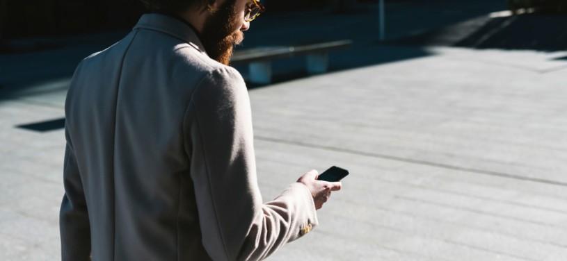Geschäftsmann mit Smartphone geht spazieren
