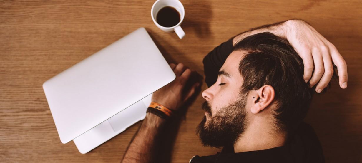 Junger Mann liegt schlafend auf dem Schreibtisch