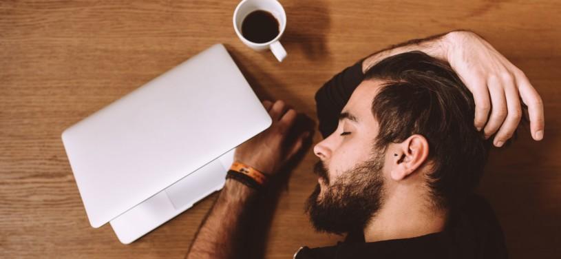 Mann liegt auf dem schlafend auf dem Schreibtisch