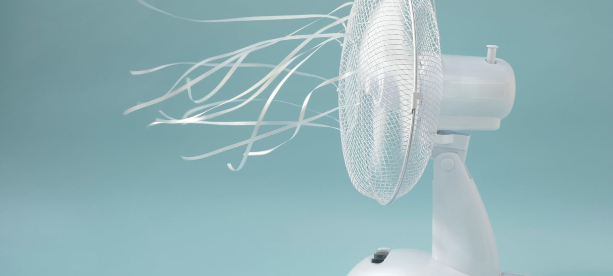 Ribbons tied to a white electric fan flutter as the fan spins