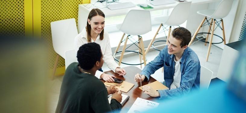 Blick von oben auf eine Gruppe junger multiethnischer Freunde, die mit Notizbüchern am Tisch in einer Bibliothek sitzen und lächeln