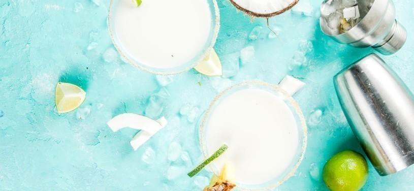 Tropisches Getränk, Gefrorene Kokosnuss-Ananas-Margaritas mit gefrorener Pina Colada, Tequila, Ananassaft und Limette, hellblauer Hintergrund, Kopierraum Draufsicht