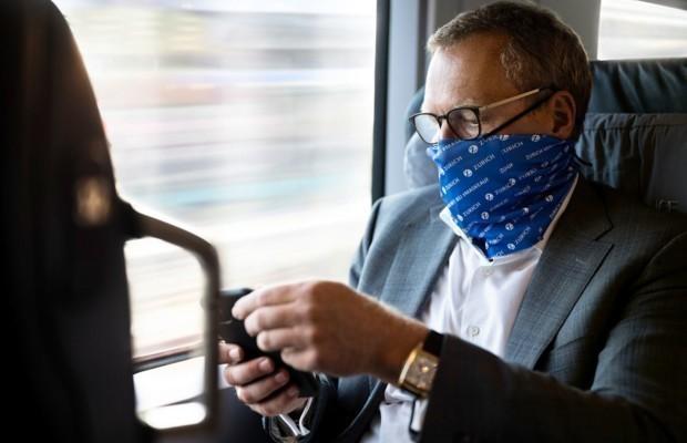 Mann sieht auf sein Handy im Zug