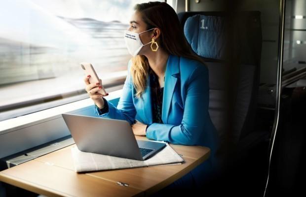 Frau sitzt mit Maske im Zug, Handy in der Hand, blickt nach draußen