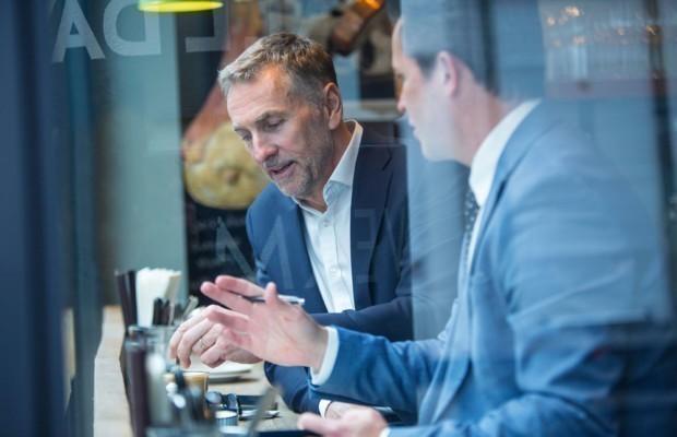 Zwei Geschäftsleute diskutieren am Fensterplatz eines Restaurants