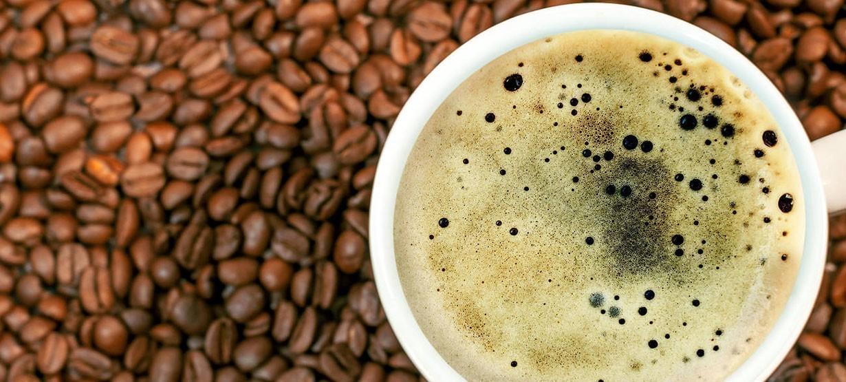 Kaffeebohnenhintergrund mit einer Tasse frischem, heissen Kaffee