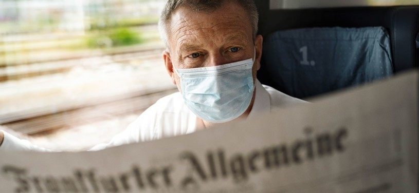 Mann mit Maske liest Zeitung Frankfurter Allgemeine im Zug