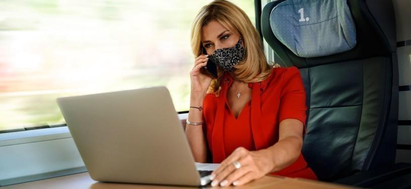 Frau mit Maske sitzt am Laptop im Zug