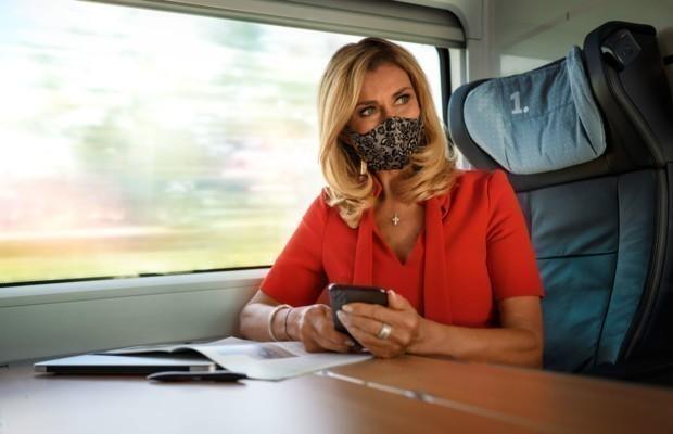 Frau mit Maske hält ein Handy in der Hand und sitzt im Zug