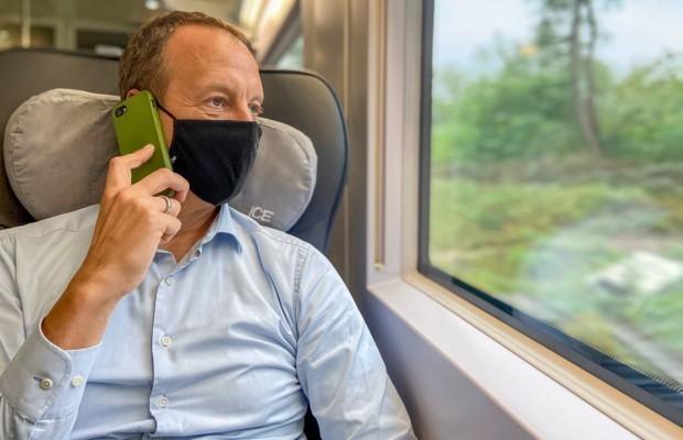 Mann mit Maske telefoniert im ICE guckt nach draußen