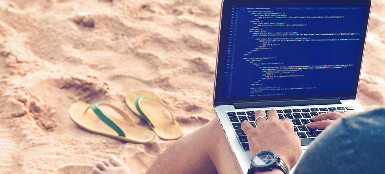 Ein Programmierer Tippen Quellcodes am Strand in einer entspannten Arbeitsumgebung. Studieren, Arbeiten, Technologie, Freelance Work Konzept.