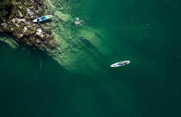 Ein nackter Mann schwimmt im Walchensee, die Frau liegt am Stand-Up-Paddle-Board, Walchensee, Bayern, Deutschland.