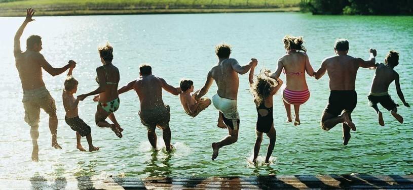 Rückansicht einer großen Familiengruppe, die gemeinsam in einen See springt